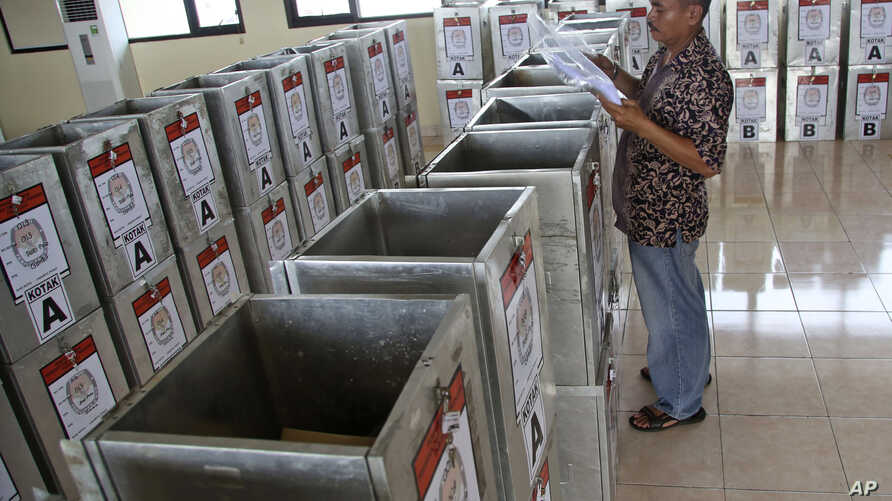 An electoral worker sorts documents to be put inside ballot boxes and distributed to polling stations at a government office in Jakarta, Indonesia, July 7, 2014.