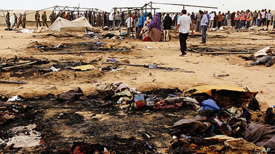 Refugees gather near burnt tents at Choucha camp in Tunisia near the Libyan border, May 22, 2011