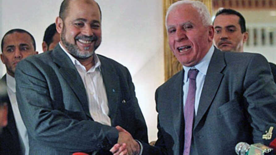 Palestinian Fatah delegation chief Azzam al-Ahmed (R) shakes hands with Hamas deputy leader Mussa Abu Marzuq after a joint press conference in Cairo on April 27, 2011 as rival Palestinian groups agreed to set up a transitional unity government and ho