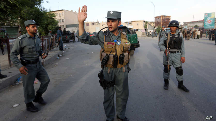 FILE - Afghan security forces stand guard at site of suicide car bombing attack in Kabul, May 19, 2015.