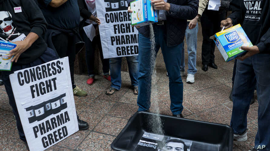 AIDS activists pour cat litter on an image of Turing Pharmaceuticals CEO Martin Shkreli in a makeshift cat litter pan during a protest highlighting pharmaceutical drug pricing, in front of the building that houses Turing's offices, in New York.