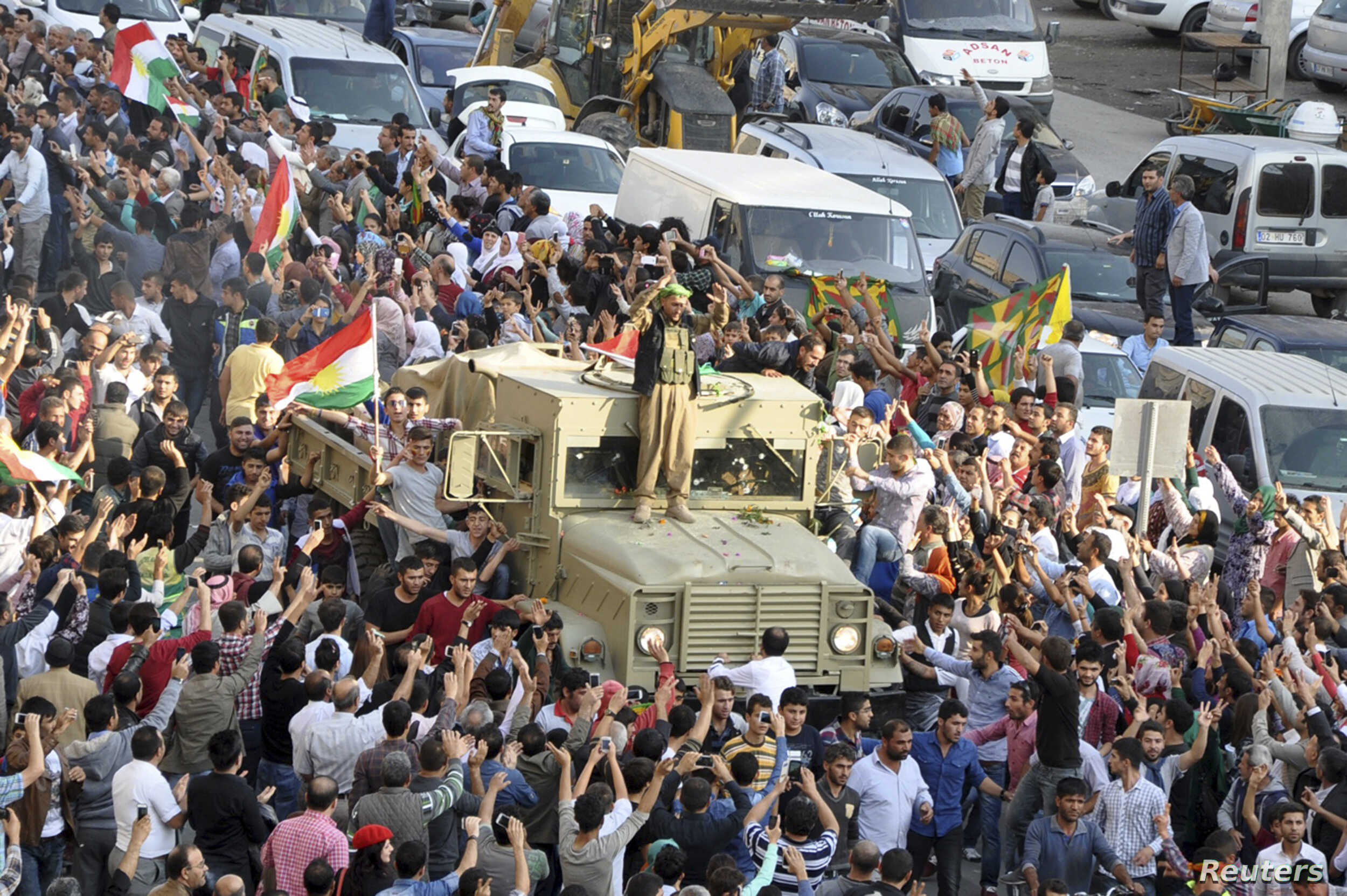 Convoy of peshmerga vehicles is escorted by Turkish Kurds on their way to the Turkish-Syrian border, in Kiziltepe, near the southeastern city of Mardin, Oct. 29, 2014.