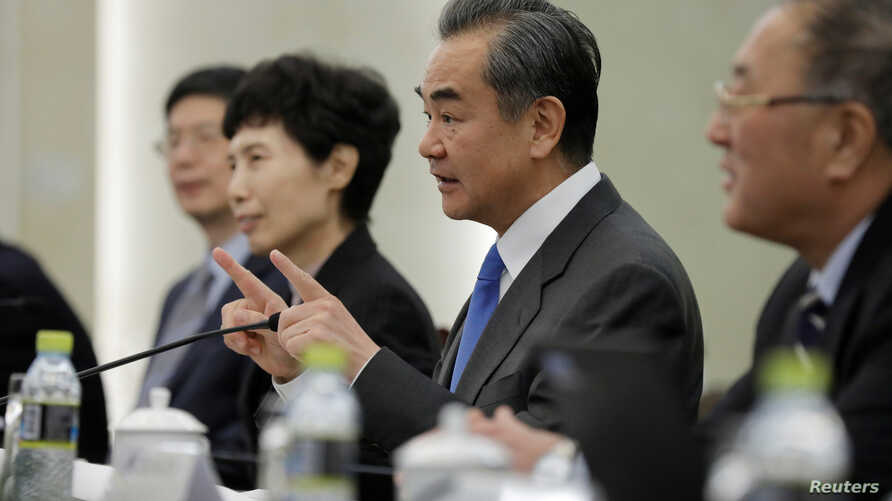 Chinese State Councilor and Foreign Minister Wang Yi (2-R) speaks during a meeting with Myron Brilliant, executive vice president and head of International Affairs at the U.S. Chamber of Commerce (not pictured) at the Ministry of Foreign Affairs in B