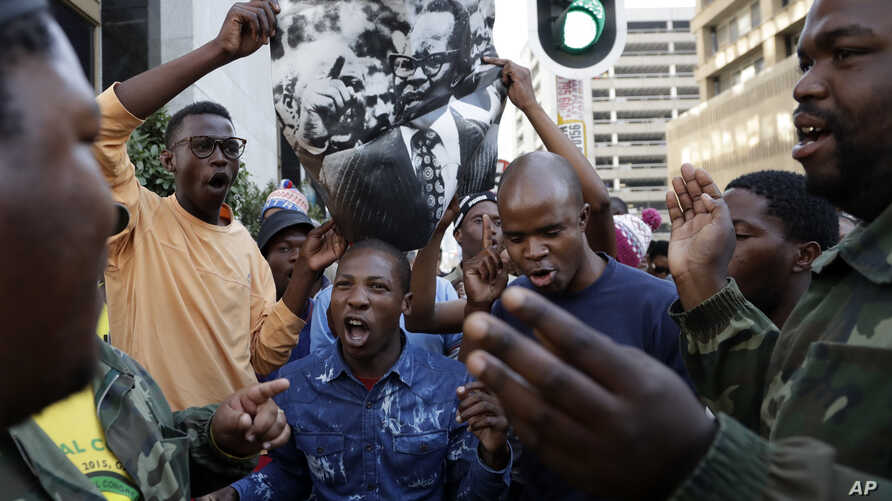 South Africa Protests: A supporter of the African National Congress, sings whilst holding a poster with the late party president Oliver Tambo's face outside the ruling party ANC headquarters in downtown Johannesburg, South Africa, Monday, Sept. 5, 20