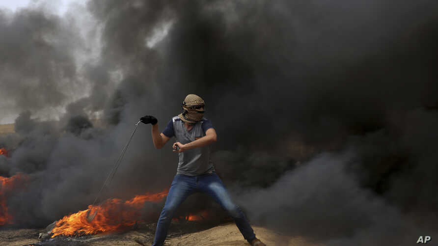 A Palestinian protester hurls stones at Israeli troops during clashes along Gaza's border with Israel, east of Khan Younis, Gaza Strip, April 20, 2018.