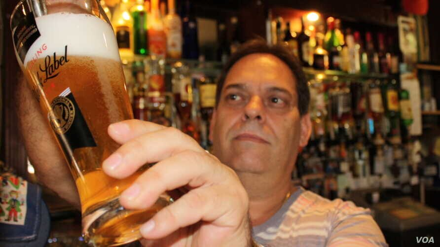 The Guildhall Bar's present owner, Fernando Coimbra, a South African of Portuguese descent, pours another pint of beer in the historical venue. Photo by Darren Taylor