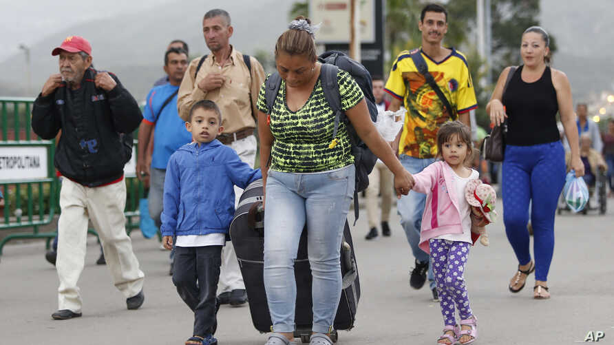 Venezuelan migrant mother Yelitza Fuenmayor crosses the Simon Bolivar International Bridge into Colombia with her children and luggage, to Cucuta, Colombia, as they leave Venezuela.