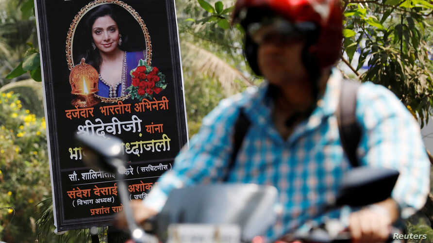 """A man rides past a poster of Bollywood actor Sridevi outside her house in Mumbai, India, Feb. 27, 2018. The poster reads """"To a quality Indian actress, Sridevi, we pay a heartfelt tribute."""""""