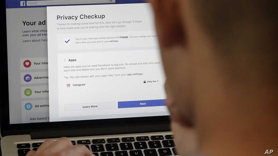 A man poses for photos in front of a computer showing Facebook ad preferences pages in San Francisco, March 26, 2018. Facebook is giving its privacy tools a makeover as it reels from criticisms over its data practices and faces tighter European regul...