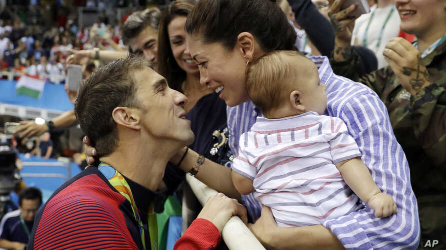 FILE - Michael Phelps celebrates winning a gold medal in the men's 200-meter butterfly with Nicole Johnson and baby Boomer during the swimming competitions at the 2016 Summer Olympics, in Rio de Janeiro, Brazil.