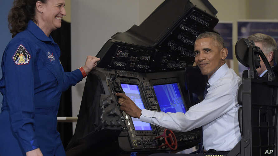 President Barack Obama sits in a flight simulator during a tour of innovation projects at the White House Frontiers Conference at University of Pittsburgh in Pittsburgh, Oct. 13, 2016, as NASA astronaut Dr. Serena Aunon-Chancellor, left, watches.