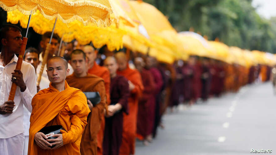 Buddhist monks walk down a road asking for alms during the annual Vesak festival, in Colombo, Sri Lanka, May 11, 2017.