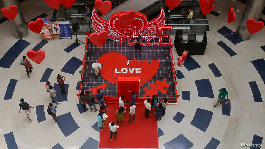 People arrange tiles of a heart-shaped puzzle during an event to promote Valentine's Day celebrations, inside a mall in Bengaluru, India, Feb. 12, 2018.
