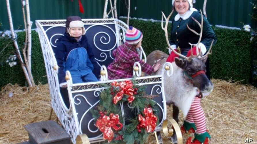 Jingles the reindeer poses with owner Sonya Benhardt and young fans at Swanson's Nursery in Seattle, Washington.