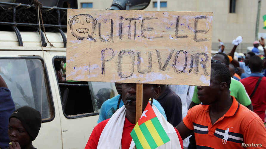 "A man holds up a sign which reads, ""leave the power,"" during opposition protest to call for the immediate resignation of President Faure Gnassingbe in Lome, Togo, Sept. 7, 2017."