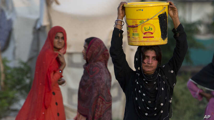A woman carries water for her family at a tube well in Rawalpindi, Pakistan, Aug. 22, 2017. A new study suggests some 50 million Pakistanis could be at risk of drinking arsenic-tainted groundwater. The findings are based on a hazard map built using w