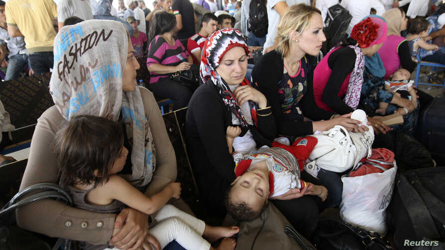 Syrian refugees, fleeing the violence in their country, wait to cross the border into the autonomous Kurdish region of northern Iraq, August 19, 2013. More than 20,000 Syrian refugees have entered northern Iraq since Thursday in one of the largest cr