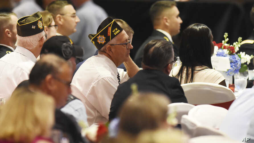 Veterans listen as President Donald Trump thanks them for their service during his remarks at a Salute to Service dinner in White Sulphur Springs, West Virginia, July 3, 2018.