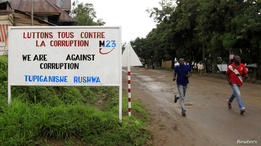 FILE - People jog past a sign, with a message by the M23 movement in their campaign against rampant corruption in the DRC, in Rutshuru town, Nov. 3, 2012.