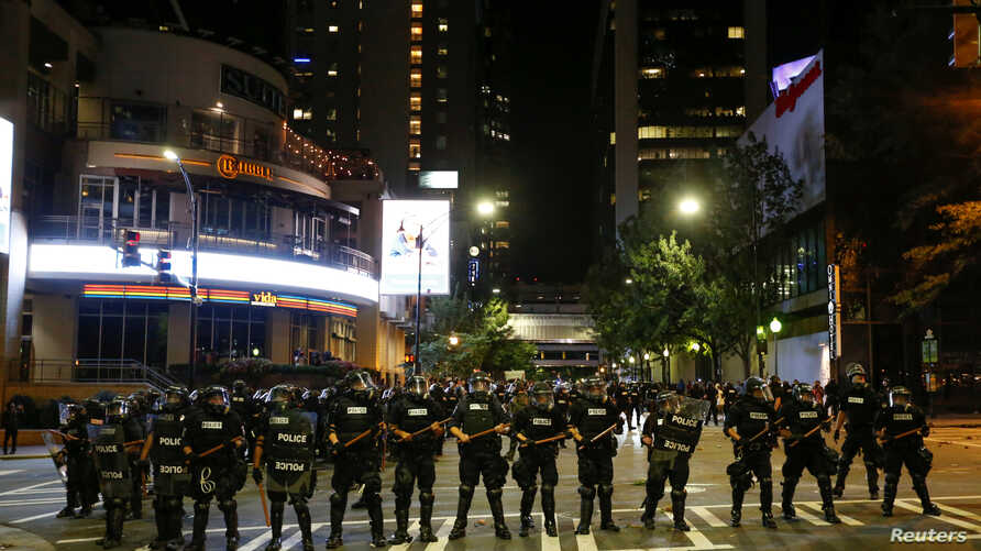 Police hold their lines in uptown Charlotte during a protest of the police shooting of Keith Scott