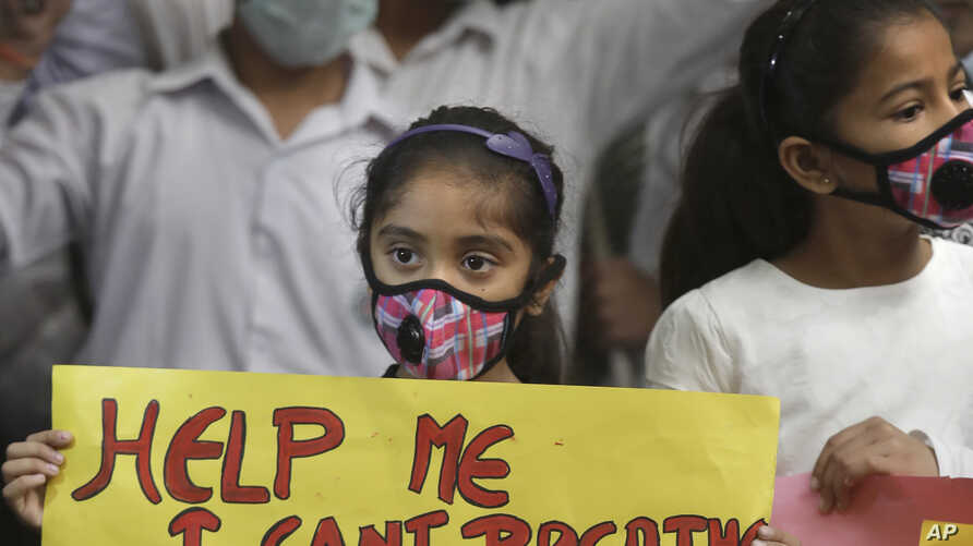 An Indian girls holds a banner during a protest against air pollution in New Delhi, India, Nov. 6, 2016.
