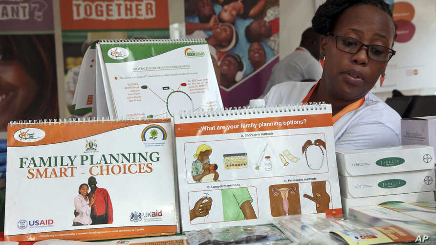 FILE - Health worker Sylvia Marettah Katende displays reproductive health products and information at a family planning exhibition in Kampala, Uganda, Sept. 26, 2017. Like Uganda, neighboring Kenya is now starting to promote vasectomies in family pla