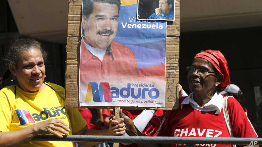 Supporters of Venezuela's President Nicolas Maduro hold a poster of him outside the Supreme Court where he is being sworn-in for another term in Caracas, Venezuela, Thursday, Jan. 10, 2019. Maduro was sworn in to a second term amid international call
