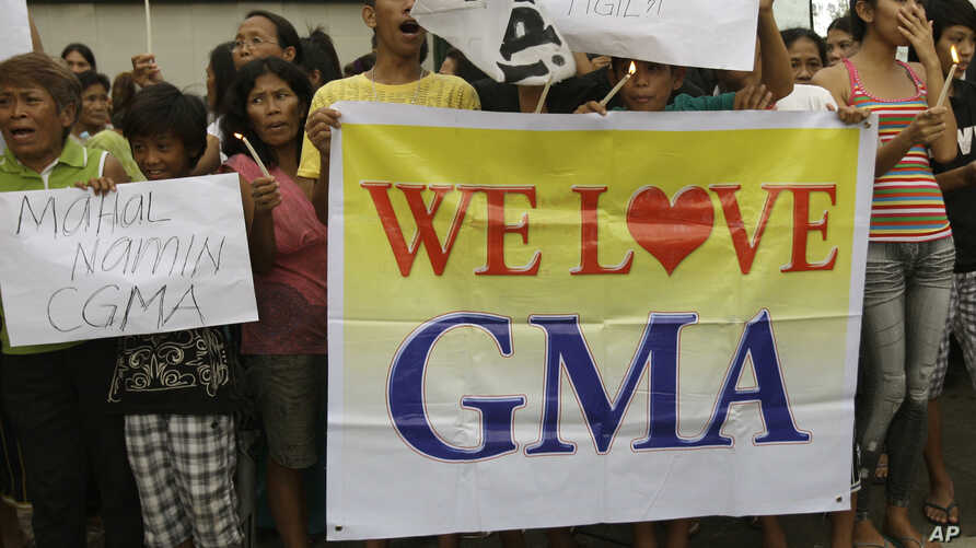Supporters of former Philippine President Gloria Macapagal Arroyo hold candles during a rally outside the Veterans Memorial Medical Center where she is now under police custody, Manila, Oct. 4, 2012.
