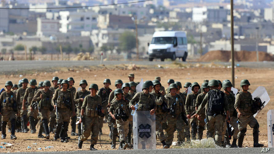 Turkish soldiers take their position a few hundreds meters from the  the Turkey-Syria border in Mursitpinar, near Suruc, as fighting intensified between Syrian Kurds and the militants of Islamic State, Oct. 5, 2014.