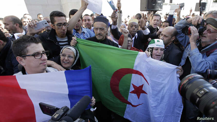 Muslims, holding French and Algerian flags, attend a gathering in front of the Paris Mosque after Friday prayers September 26, 2014, to pay tribute to Herve Gourdel, a French mountain guide who was beheaded by an Algerian Islamist group.