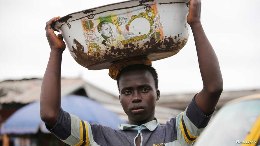 A man balances a bowl with a print of the old Nigerian naira banknote on his head at a local market in Agege district in Lagos, Nigeria, Aug. 16, 2016.