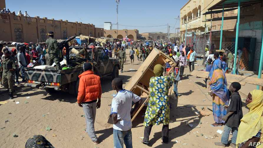 Malian troops try to dissuade the crowd from looting shops in Timbuktu, Jan. 29, 2013. Hundreds of Malians looted Arab-owned shops Tuesday in Mali's fabled Timbuktu, newly freed from Islamists.