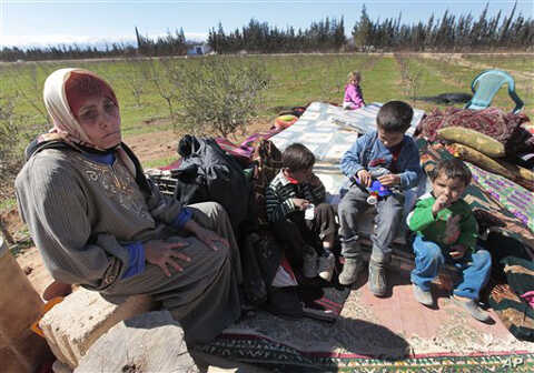 Hassana Abu Firasl, left, a Syrian woman who fled from the Syrian town of Qusair near Homs, is seen with her family at the Lebanese-Syrian border village of Qaa, eastern Lebanon,  Monday, March 5, 2012.