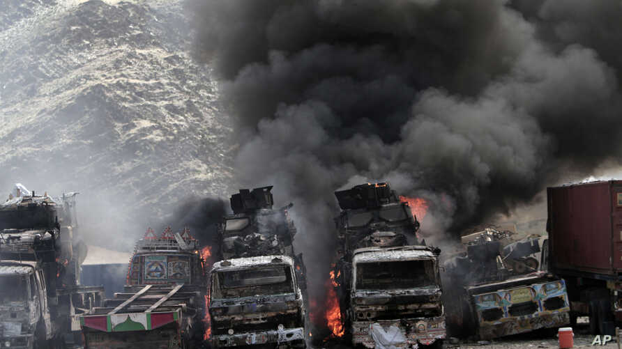 Smoke rises from  NATO supply trucks following an attack by militants in the Torkham area near the Pakistan--Afghanistan border in Jalalabad province east of Kabul, Afghanistan, Sept 2, 2013.