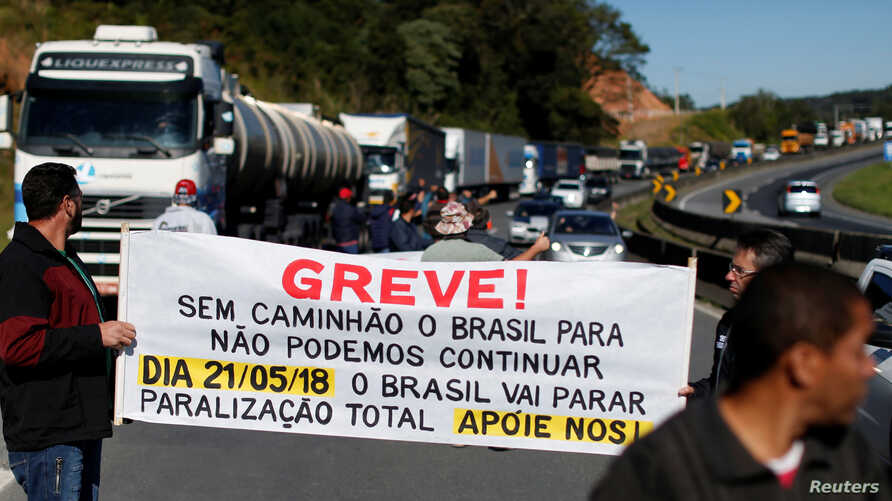 "Brazilian truck drivers blocked the BR-116 highway with their trucks during a strike in Curitiba, Brazil, May 21, 2018. The banner reads: ""Strike! Without truck, Brazil stop, we can not continue. Brazil will stop, total stoppage, support us!"""