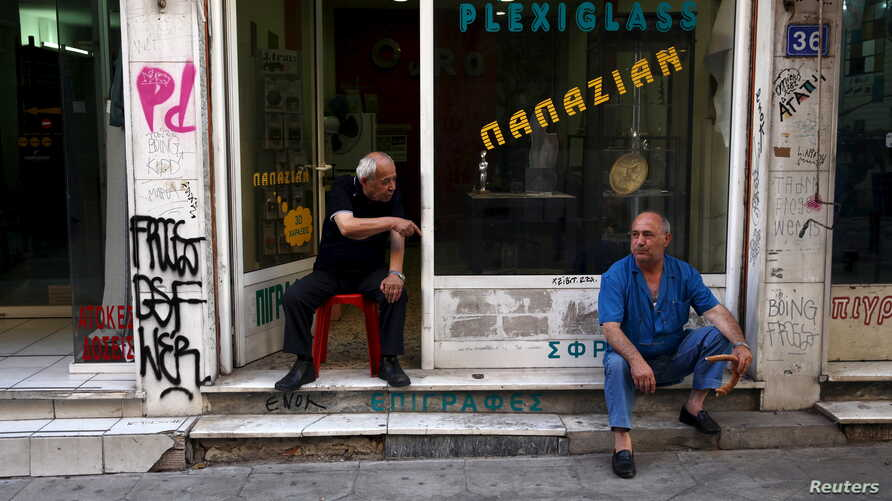 Men sit in front of a shop in central Athens, Greece, July 21, 2015.