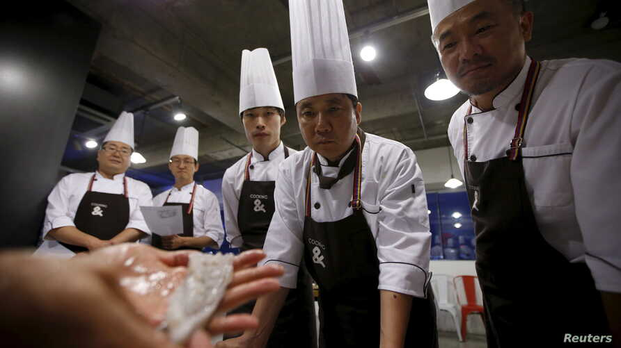 Lee Jin-soo (2nd R), 53, looks at a small octopus as he and others take part in Happy Guys Cooking Class in Seoul, South Korea, July 31, 2015.