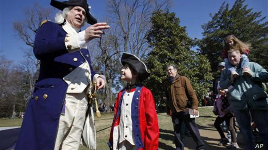Lewis Bliss, 10, of Burke, Va., dressed in a musicians outfit from the Revolutionary War era, center, meets George Washington, portrayed by Dean Malissa, during Presidents Day activities at George Washington's Mount Vernon Estate in Mount Vernon, Vir