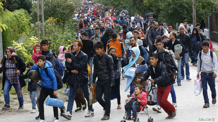 Migrants carry their belongings as they walk towards the Austrian border from Hegyeshalom, Hungary, Sept. 24, 2015.