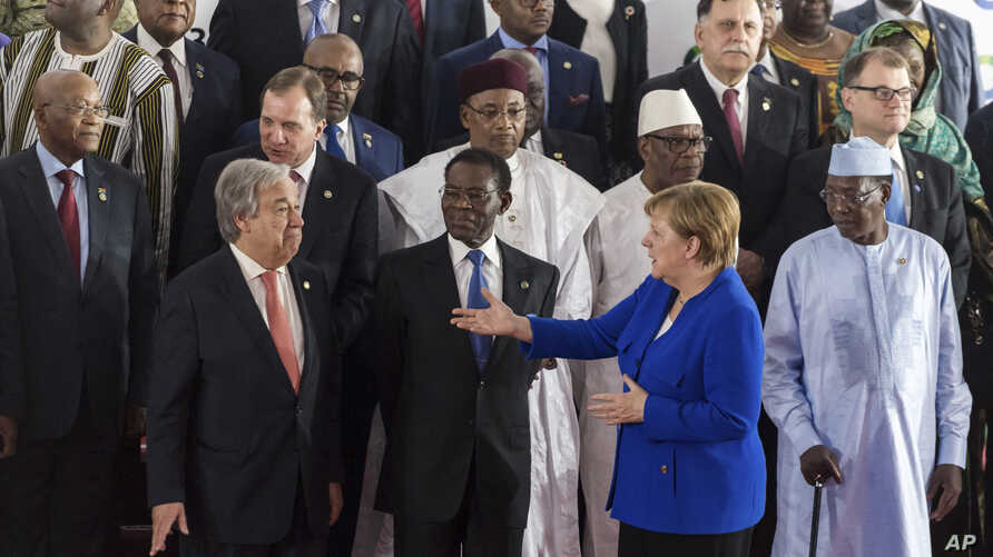 German Chancellor Angela Merkel (Front-R) speaks with United Nations Secretary General Antonio Guterres (Front-L), during a group photo at an EU Africa summit in Abidjan, Ivory Coast on Nov. 29, 2017.