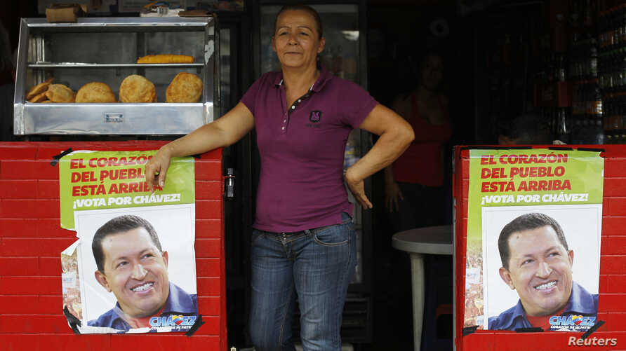 A woman stands in a restaurant between posters of Venezuela's President Hugo Chavez, in front of a military hospital, where Chavez is being treated, in Caracas, February 20, 2013.