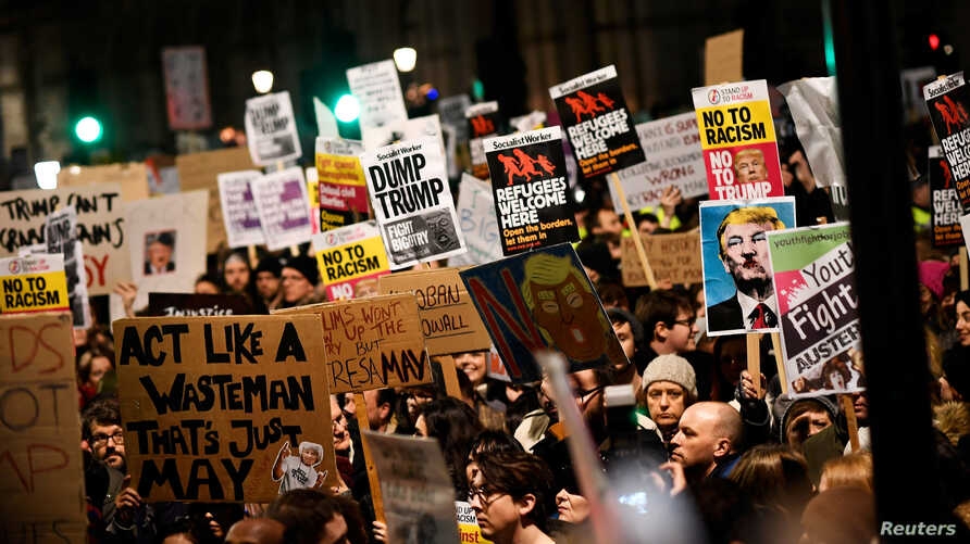 Demonstrators hold placards during a protest against U.S. President Donald Trump's executive order travel ban in London, Britain, Jan. 30, 2017.