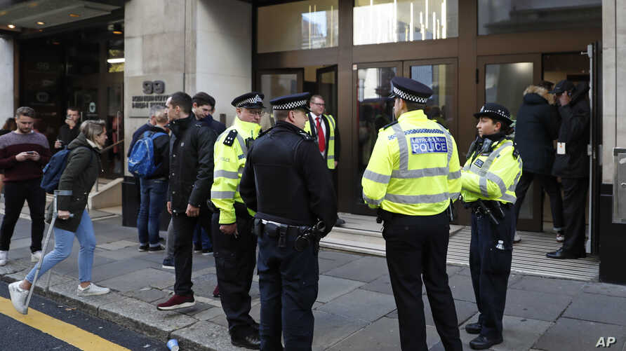 Police officers and security watch as people re-enter a building after a stabbing incident in central London, Friday, Nov. 2, 2018.