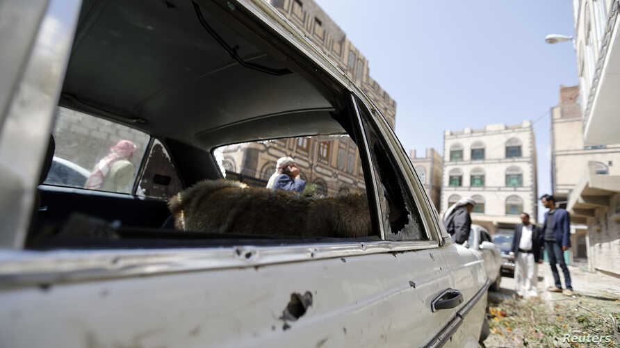 People gather near a car damaged by a mortar shell during fighting between Shi'ite Houthi militants and government forces in Sanaa, Sept. 19, 2014.