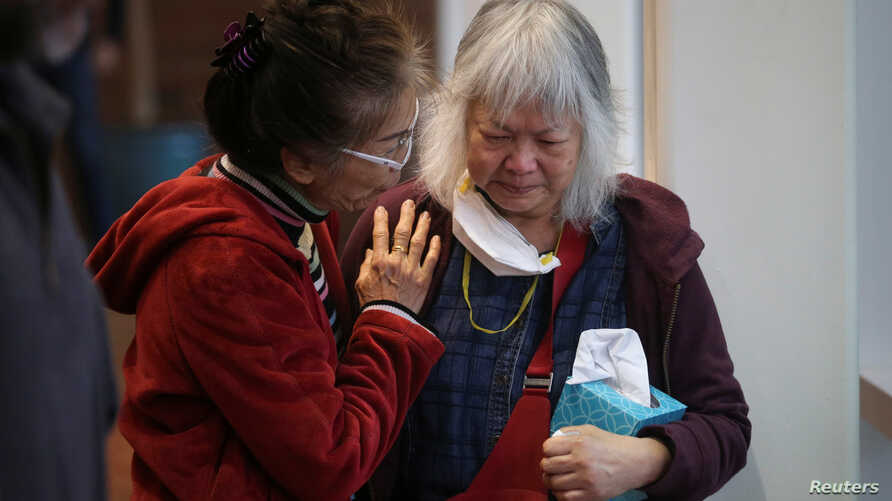 """A woman comforts Colleen Love, right, who lost her home in the Camp Fire, at a """"Thanksgiving Together"""" dinner put on by World Central Kitchen at Chico State University in Chico, California, Nov. 22, 2018."""
