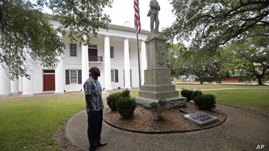 In this Aug. 1, 2018 photo, Ronnie Anderson, an African-American man charged with possession of a firearm by a convicted felon, waits next to a confederate statue on the lawn of the East Feliciana Parish Courthouse in Clinton, La.