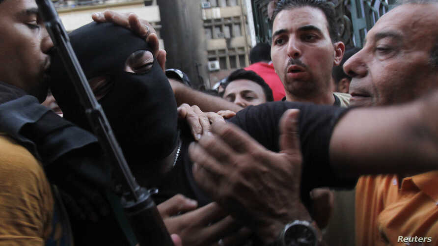 Egyptian forces member moves through crowd of interim government supporters near al-Fath mosque, Cairo, Aug. 17, 2013.