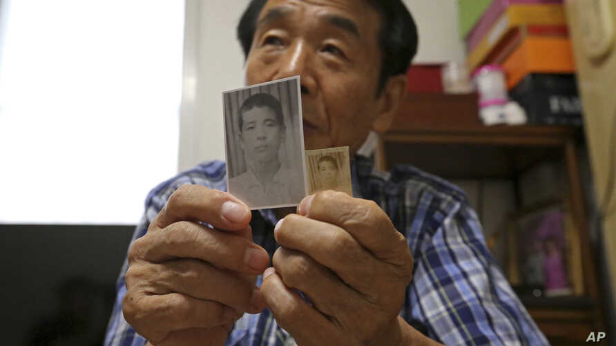 In this Aug. 17, 2018, photo, Lee Soo-nam shows photos of his brother Ri Jong Song in North Korea during an interview at his home in Seoul. Lee is among about 200 war-separated S. and their family members who are crossing into N. Korea for heart-wren