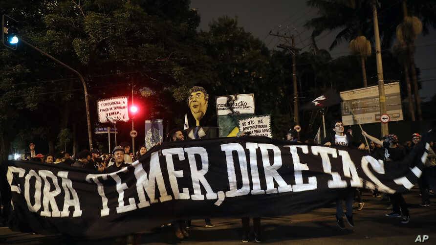 """Demonstrators protest holding a banner that reads in Portuguese """"Get out Temer, elections now,"""" outside the residence of Brazil's President Michel Temer during a general strike in Sao Paulo, Brazil, April 28, 2017. Buses, trains and metros have been ..."""