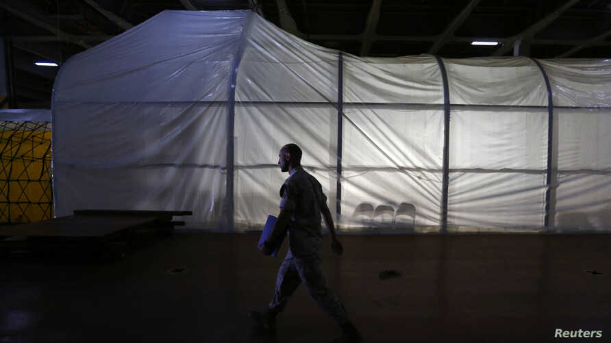 FILE - A U.S. marine officer walks past the Field Deployable Hidrolysis System (FDHS) of the U.S. MV Cape Ray ship docked at the naval airbase in Rota, near Cadiz, southern Spain.